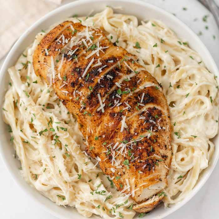 white bowl of alfredo with sliced chicken on top