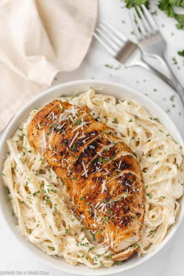 bowl of alfredo with blacked chicken on top