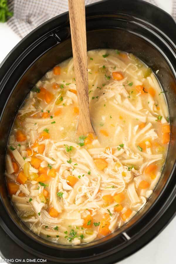 Close up image of chicken noodle soup with a brown serving spoon in the crockpot.