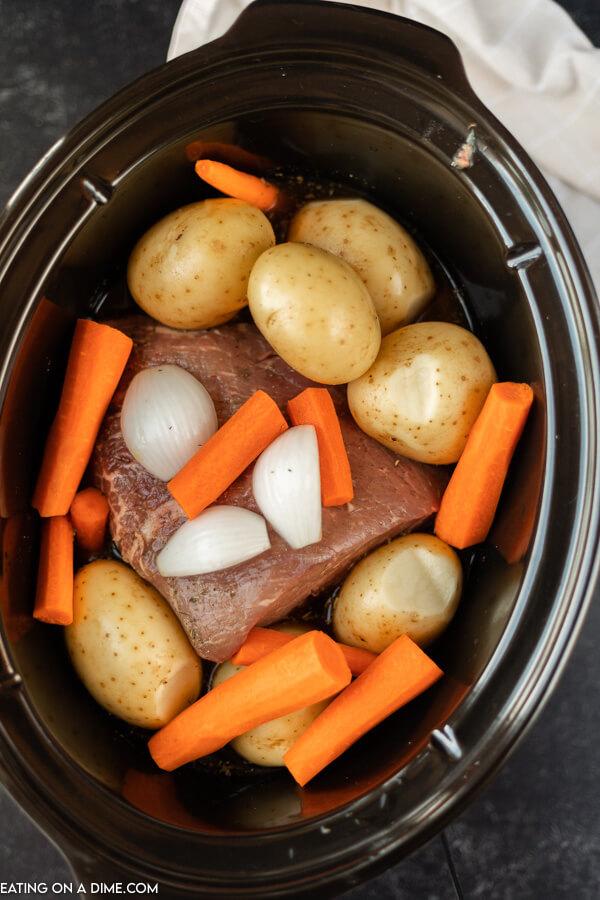 crockpot of roast, potatoes, onion and carrots