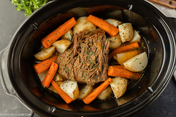 crockpot of cooked roast, carrots and potatoes