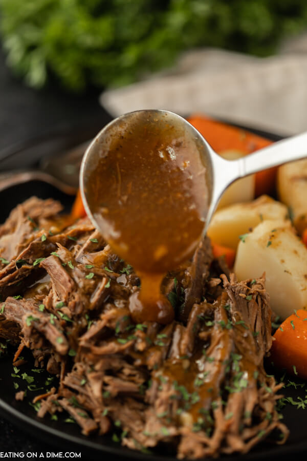 plate of roast with gravy and carrots and potatoes