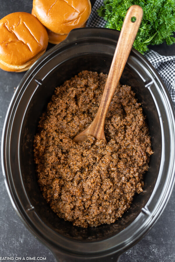 Close up image of sloppy joes in a crock pot with a brown spoons. Hamburger buns are also pictured next to the slow cooker.