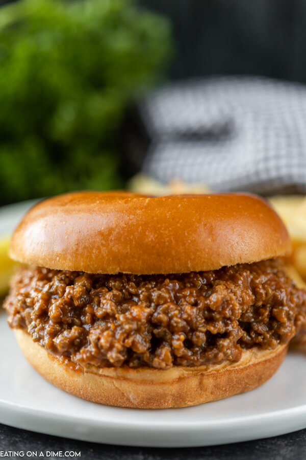 Close up image a sloppy joes on a bun plated on a white plate.