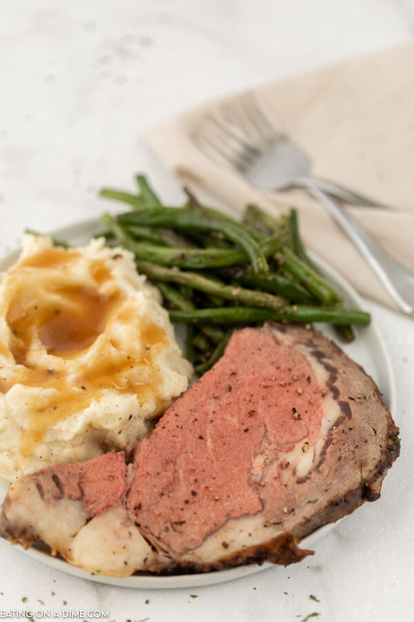 plate of prime rib, green beans and mashed potatoes