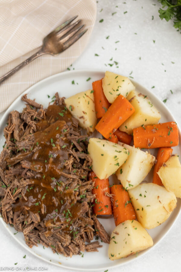 Plate with roast and gravy beside carrots and potatoes.