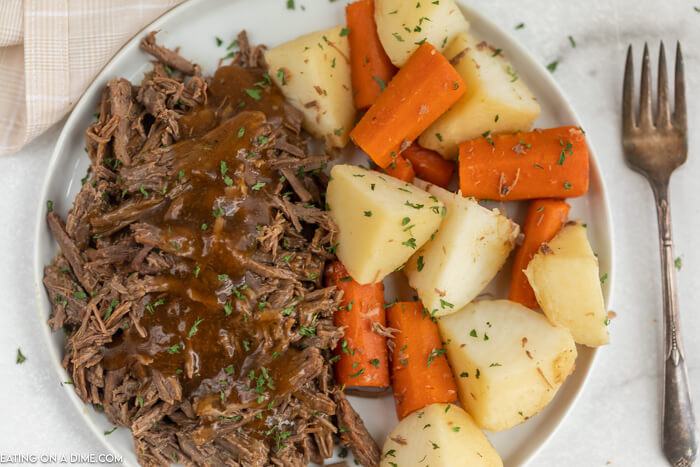 White plate with shredded roast topped with gravy beside carrots and potatoes.