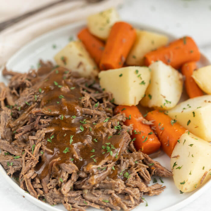 Plate with roast topped with gravy served with potatoes and carrots.