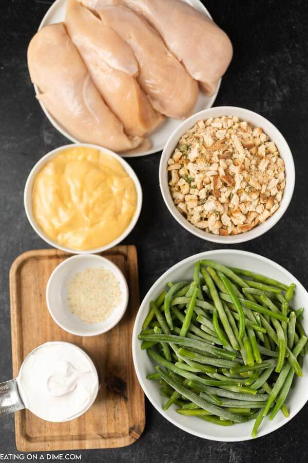 Close up image of ingredients for chicken and stuffing, It includes, frozen green beans, stuffing, chicken breast, cream of chicken soup, sour cream and seasoning.