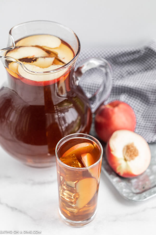 Close up image of a glass of tea with peaches in it. Also a pitcher of tea with peaches on the side.