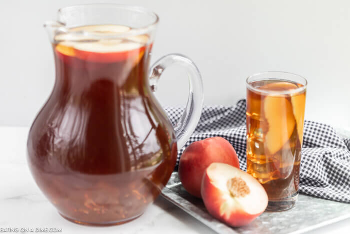Close Image of a glass serving pitcher of tea. Also a glass of tea withe peaches on a platter.