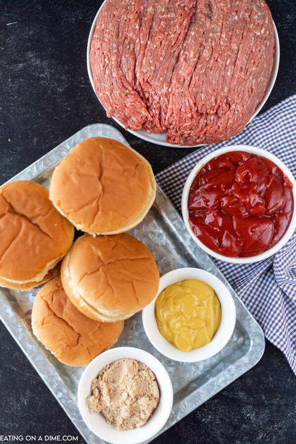 Close up image of ingredients for sloppy joes with hamburger buns on a platter.