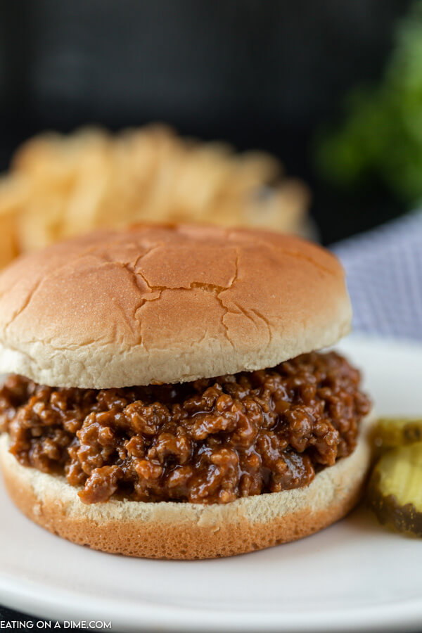 Close up image a sloppy joes on a hamburger bun with a side of pickles.