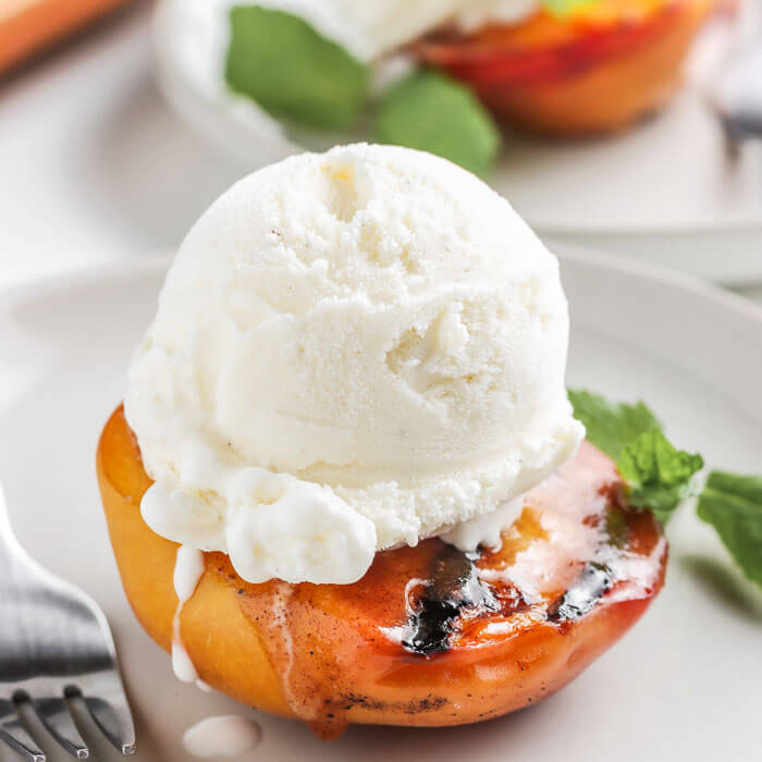 close up picture of grilled peach with ice cream