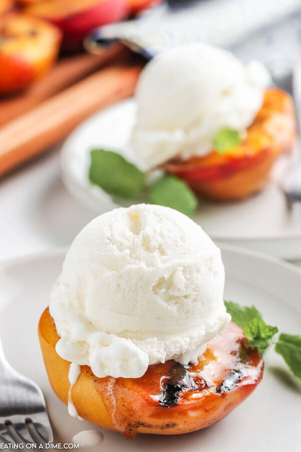 grilled peaches on a plate topped with a scoop of vanilla ice cream