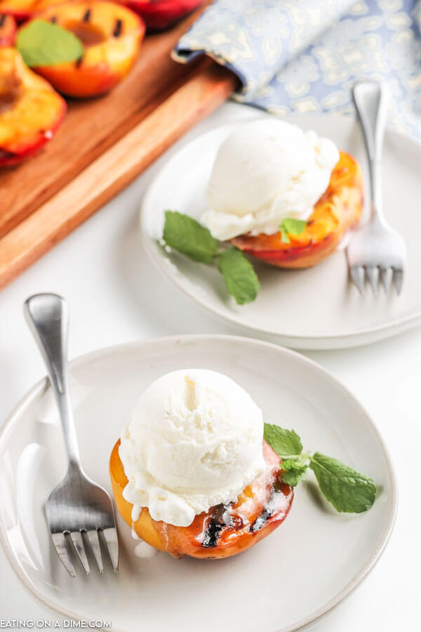 grilled peach topped with ice cream on a plate