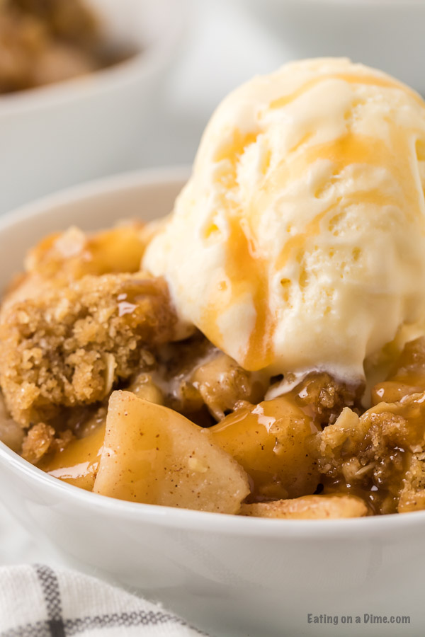 bowl of apple crisp with ice cream and caramel sauce