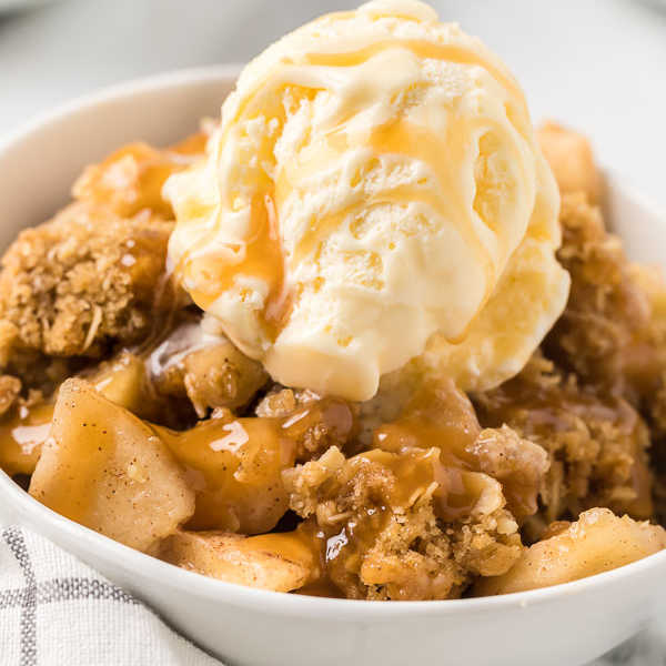 bowl of apple crisp with ice cream and caramel
