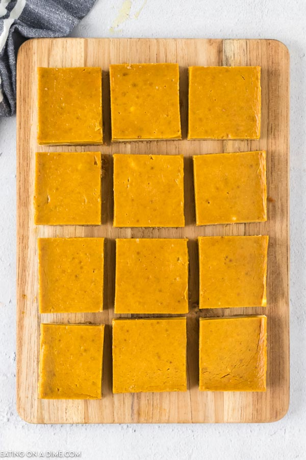 Close up image a pumpkin cheesecake bars cut into individual size on a serving tray.