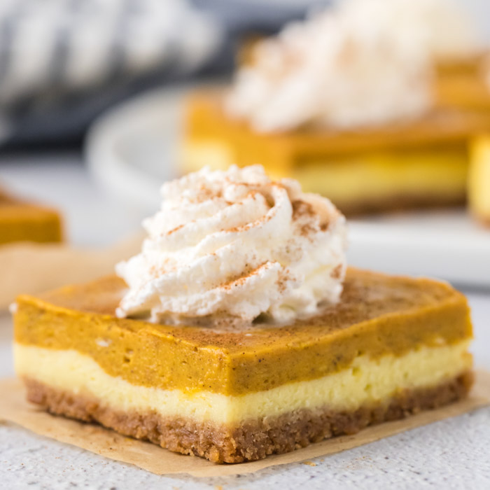 Close up image of a square piece of pumpkin cheesecake bars with whipped topping.