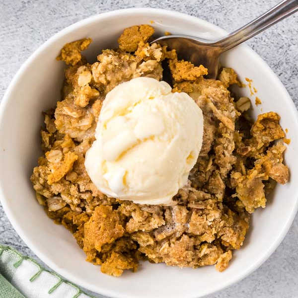 bowl of pumpkin crisp topped with ice cream