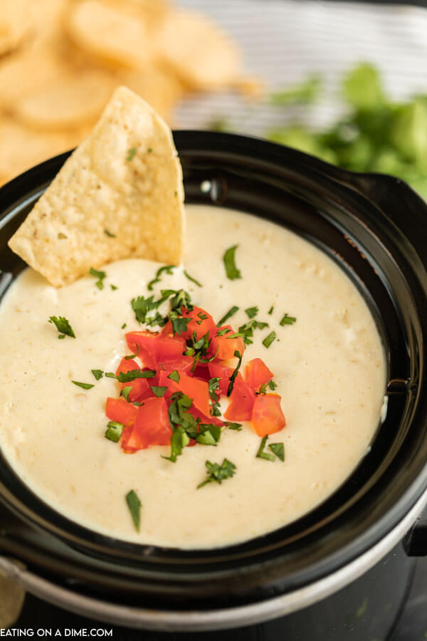 White Cheese Dip in a small crock pot topped with diced tomatoes, cilantro and a chip dipped into it.