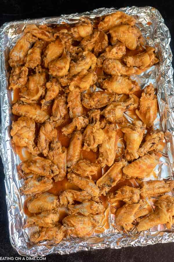 Chicken wings on a foil lined baking sheet ready to be broiled.