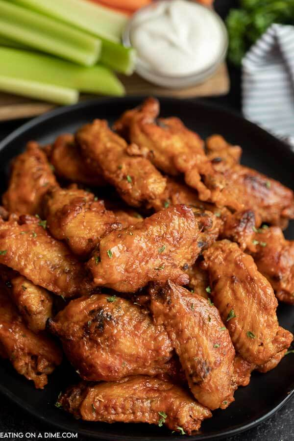 Platter of chicken wings with celery behind it.