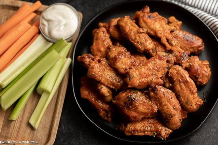 Platter of chicken wings beside cut up veggies and ranch dressing.