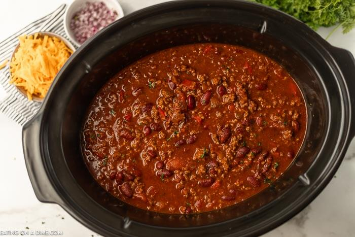 Cooked cowboy chili in a crock pot with shredded cheese and red onions next to it.