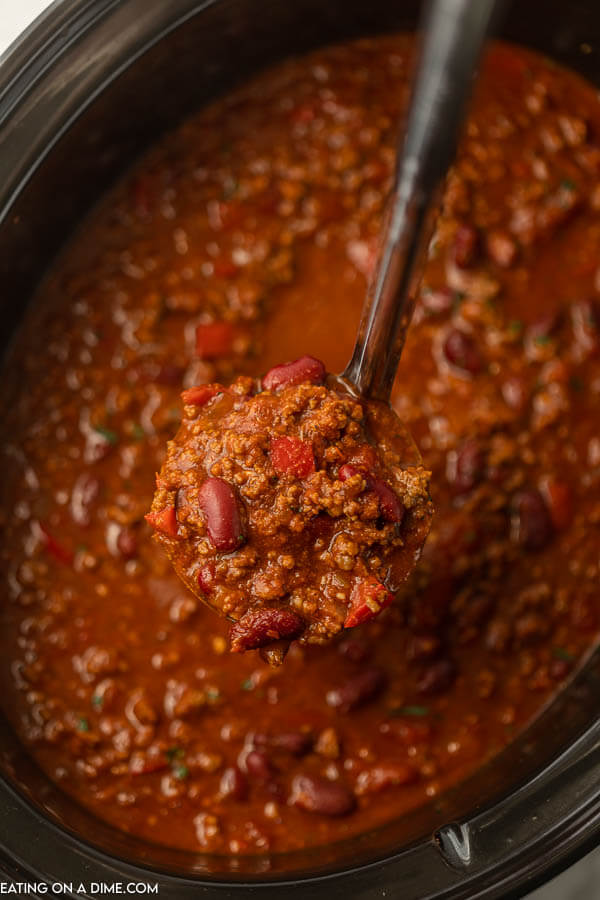 A large ladle full of crock pot chili scooping a portion of the chili out of the crock pot.