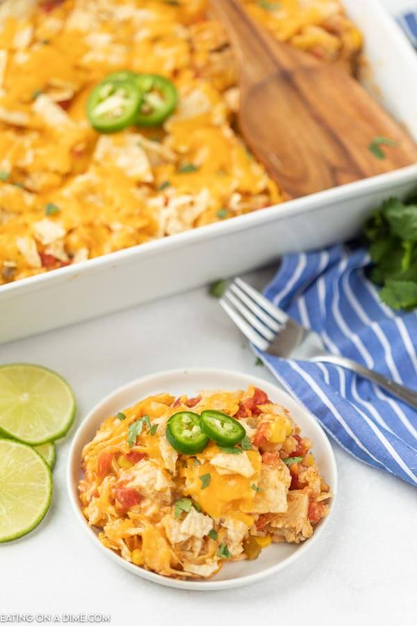 Nacho Chicken Casserole Recipe in a white baking dish with a white plate in front of it with chicken casserole.