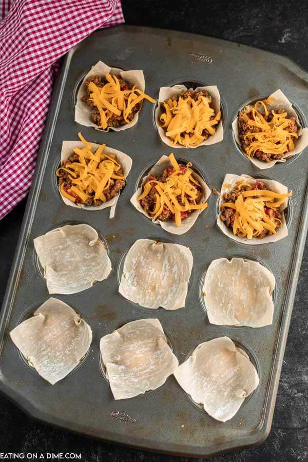 You will love these easy Wonton Taco Cups. This recipe has lots of cheese and yummy taco meat, veggies and more! Give it a try.