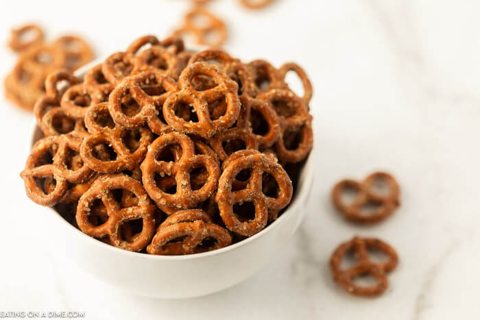 Overview of these seasoned pretzels in a white bowl on a white countertop