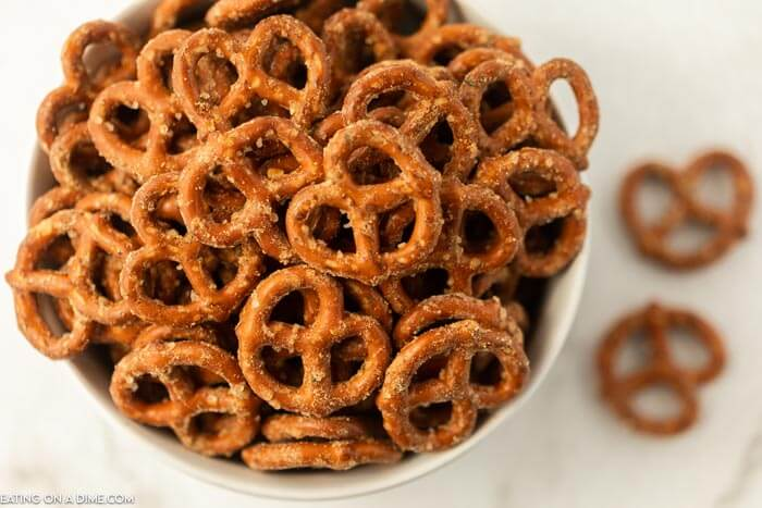Close up of a bowl of ranch pretzels with a few on the counter next to the bowl.